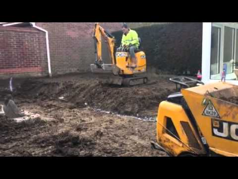 D.M.S Micro Digger Hire. Micro digger manoeuvring from one level to another