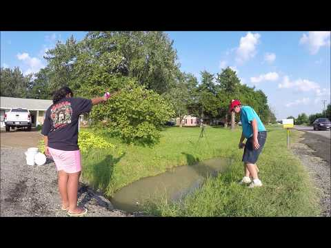 Fishing for crawfish in a ditch with a rod and reel