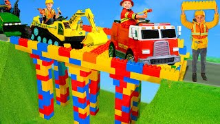 Les enfants construisent un pont avec une pelle, des camions de pompiers Kids build bridge with toys
