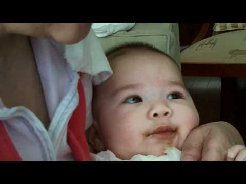Baby drinking prune juice and making faces