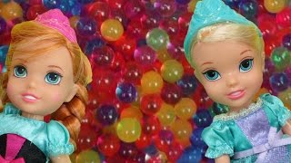 Elsa and Anna toddlers have fun in ORBEEZ ! They slide into colorful water beads!