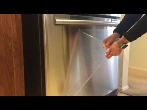 Removing the plastic film on new fridge.