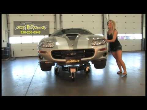 Girl moves car with rolling jack stand