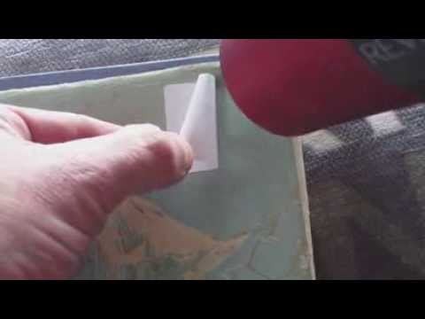 REMOVING A SELF ADHESIVE PRICE LABEL FROM OLD BOOK PAPER JACKET BY HAIRDRYER