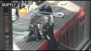 Climate change protesters glue themselves to train at London's Canary Wharf station
