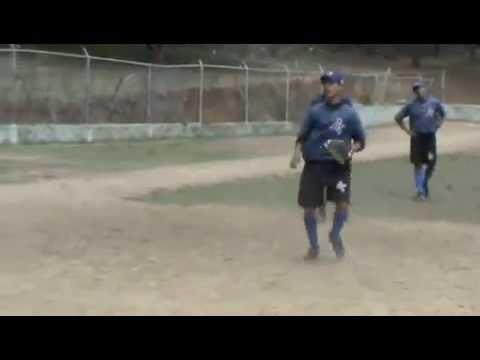 Three Dominican baseball players fielding hard hit ground balls on third base