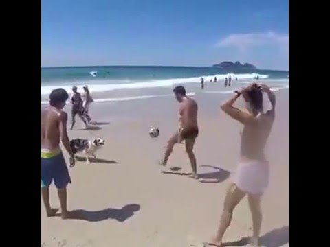 Dog joins football pssing drills with friends at the beach