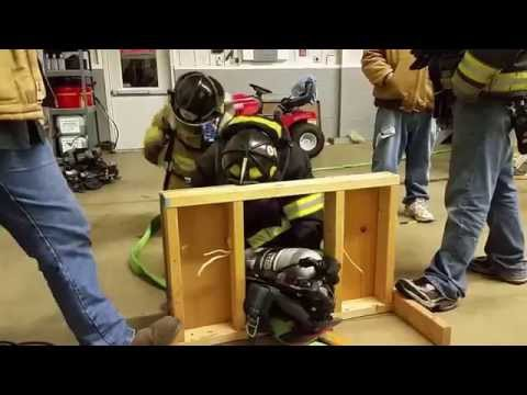 Firefighter with SCBA crawls through wall training prop