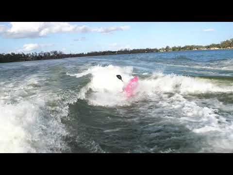 Kayaker surfing behind wakeboats