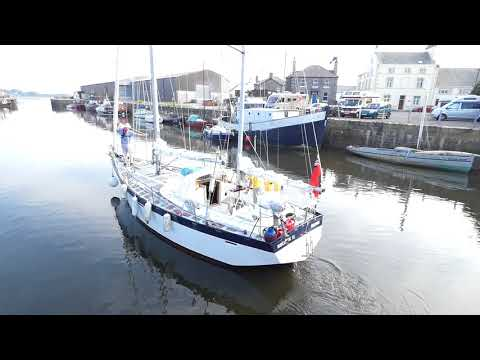 Sailing yacht boats exit Glasson Dock lock system into River Lune Lancaster England UK