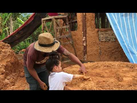 3 year old girl building a cob oven